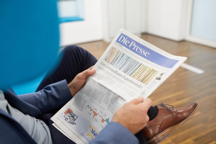 """Männliche Person liest entspannt die Titelseite von """"DiePresse"""""""