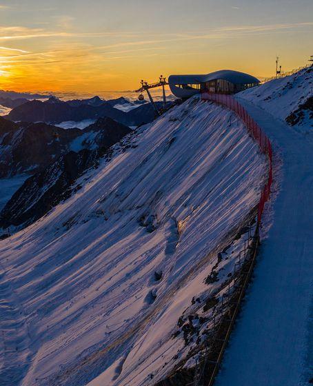Sonnenaufgang über dem Skigebiet Pitztaler Gletscher (im Bild die Bergstation der Wildspitzbahn).