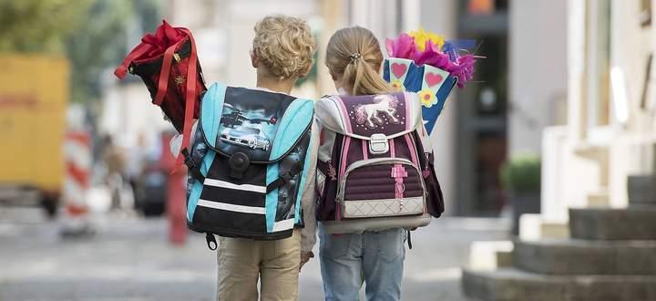 Zwei Kinder mit Schultuete auf Schulweg, von hinten (model-released) *** Two children with school bag on their way to s