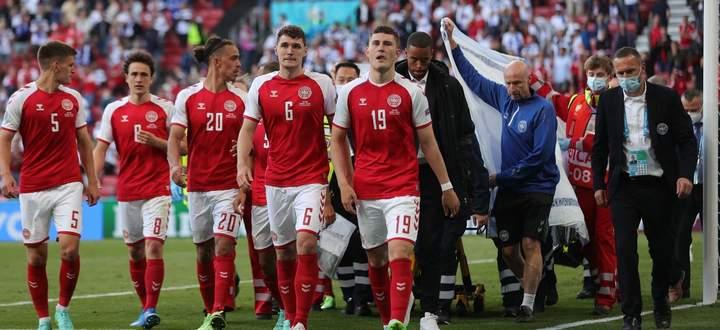 Zusammenhalt: Dänemarks Spieler begleiten den auf der Trage abtransportierten Eriksen vom Feld des Parken-Stadions.