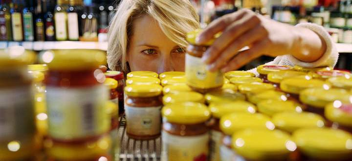 Young woman selecting jar from shelf in shop (focus on woman´s face)