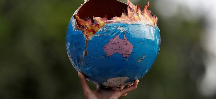 A participant holds a replica depicting globe on fire during a ´Fridays for Future´ march calling for urgent measures to combat climate change, in Mumbai