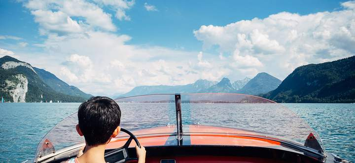 Young boy driving electric speedboat