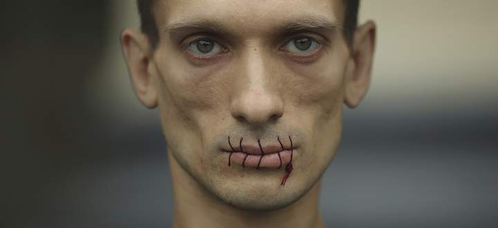 Artist Pavlensky, a supporter of jailed members of female punk band ´Pussy Riot´ looks on with his mouth sewed up as he protests outside the Kazan Cathedral in St. Petersburg