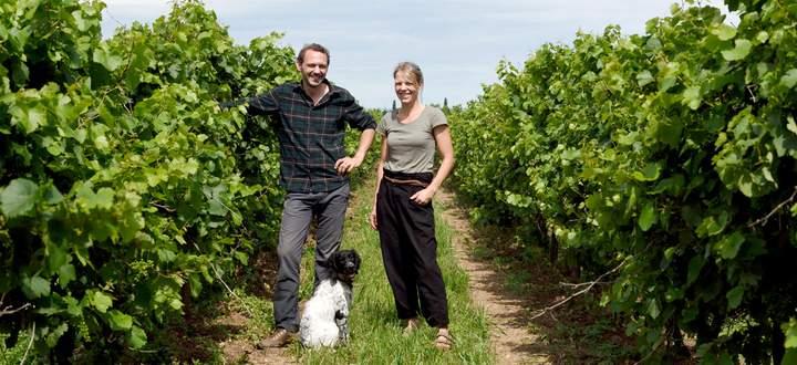 Werner und Angela Michlits (mit Hund Nala) im Weingarten, bei den wild wachsenden Reben.