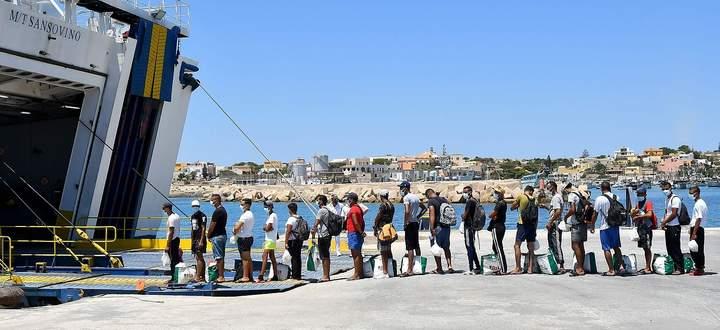 Migranten und Flüchtlinge stellen sich an, um von den Behörden per Fähre von Lampedusa weiter nach Sizilien gebracht zu werden.