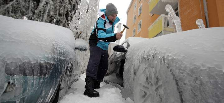 Man removes ice from an ice-covered car with a hammer in Postojna