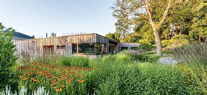 Holzhaus in Hannover eingebettet in eine Stauden- und Gräserbepflanzung.