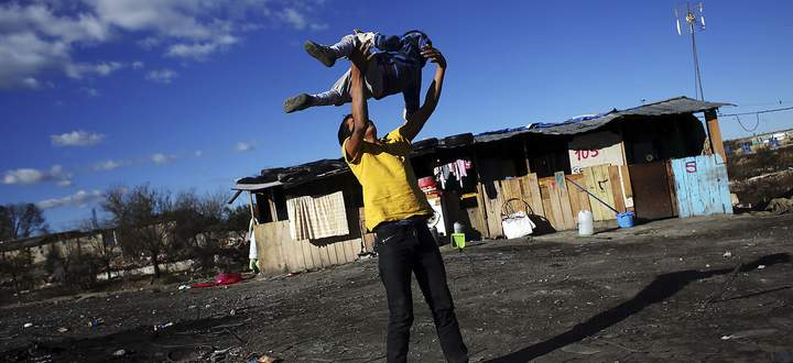 Leon throws his brother Samuel in the air as they play outside their home in the shanty town settlement of El Gallinero, in the outskirts of Madrid