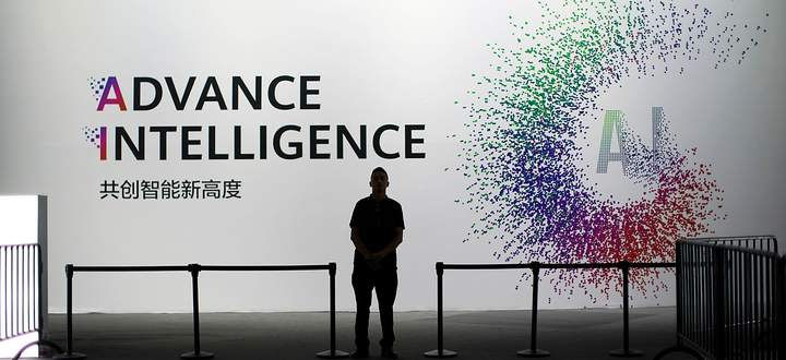 A security officer keeps watch in front of an AI (Artificial Intelligence) sign at the annual Huawei Connect event in Shanghai