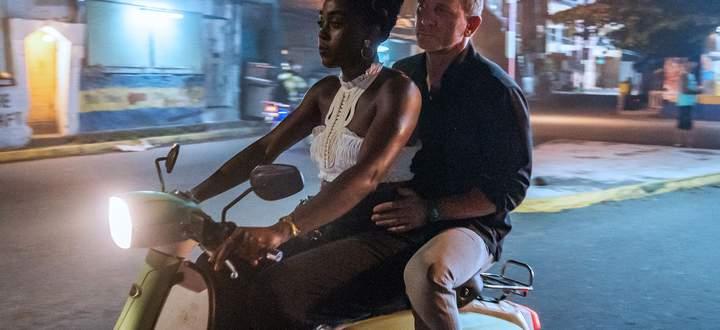 """Kein alltäglicher Anblick: James Bond (Daniel Craig) als Beifahrer auf einem Moped im neuen Film """"Keine Zeit zu sterben"""". Am Steuer: Lashana Lynch."""