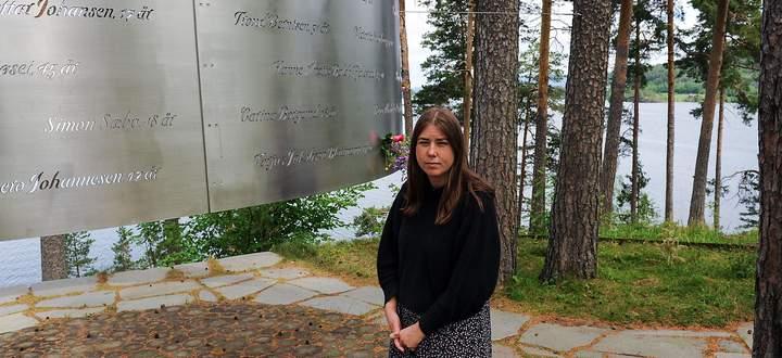 Eine Überlebende des Attentats vor einer Gedenktafel für die Ermordeten.