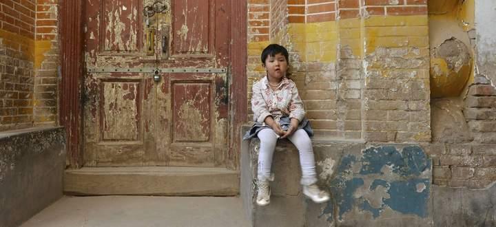 Kleines Mädchen sitz auf Backsteinfassade in den Gassen eines uigurischen Wohnviertels,
