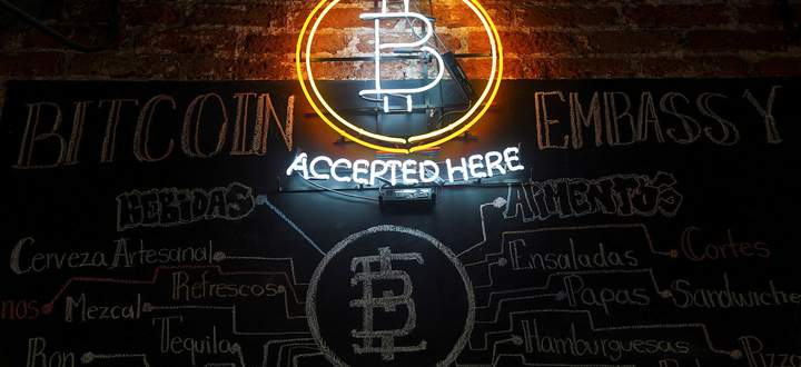 A neon logo of virtual cryptocurrency Bitcoin is seen at the Bitcoin Embassy bar in this illustration