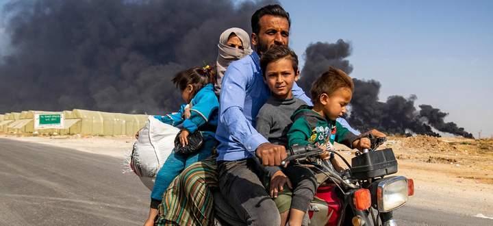 Eine Familie flieht vor türkischen Truppen in Nordsyrien.