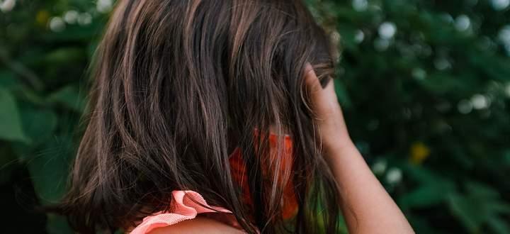 little girl in orange mask covering her eyes