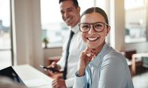 Businesswoman smiling while working with a colleague in an offic