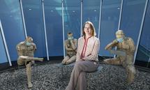 """Denker mit Denkerin - die Star-Scoutin Sarah Kiparski zwischen den steinernen """"Thinkers at Work"""" von Ucki Kossdorff in der Mitte des Congress Centrum Alpbach."""