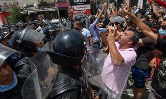 Sicherheitskräfte halten aufgebrachte Demonstranten vor dem Parlament in Tunis in Schach.