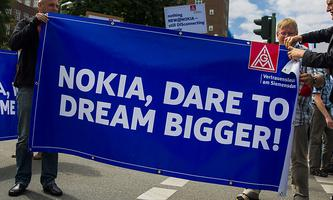 Nokia employees unfold banners during protest denouncing plans to cut jobs at Nokia´s Berlin branch in Berlin