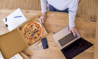 Woman at home office using laptop while eating pizza top view model released Symbolfoto property re