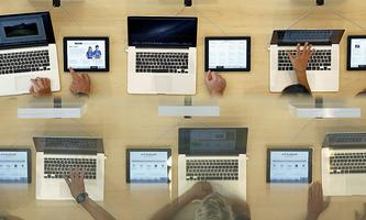 Customers look at MacBook Pros, during the official opening of the largest Apple shop in southern Europe, at Passeig de Gracia in Barcelona