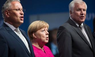 """Angela Merkel beim Singen der Nationalhymne Deutschlands. Sie will es bei """"brüderlich mit Herz und Hand"""" belassen."""