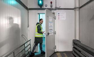 A KLM worker is entering a cold room at Amsterdam's Schiphol Airport