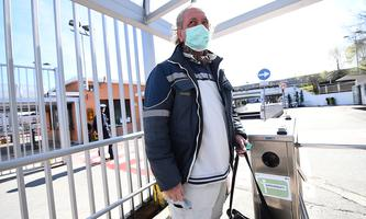 FILE PHOTO: Fiat Chrysler Automobiles (FCA) worker, wearing a protective face mask, leaves a Mirafiori plant, after the Italian government puts the whole country on lockdown as new coronavirus cases surge, in Turin