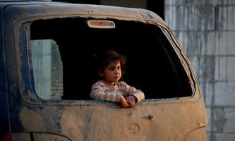 An internally displaced Syrian girl inspects the area from a broken window of a van in an IDP camp located near Idlib