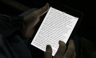 A man reads the bible from an iPad mini at the ´Christ is the Answer International Ministries´ group´s camp near Florence