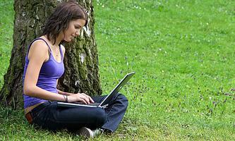 Junge Freau sitzt mit einem Notebook in einer Wiese