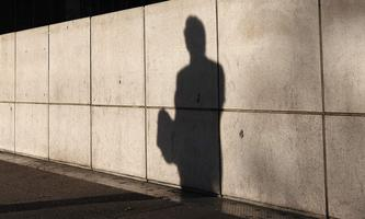 The shadow of a man is cast on a wall at Canary Wharf financial district