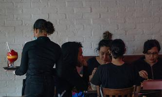 September 30, 2020, New York, New York, USA: A waitress serves a drink to customers inside at the Dallas BBQ in Chelsea