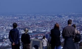 People enjoy a sunny autumn day as they look down on the city of Vienna