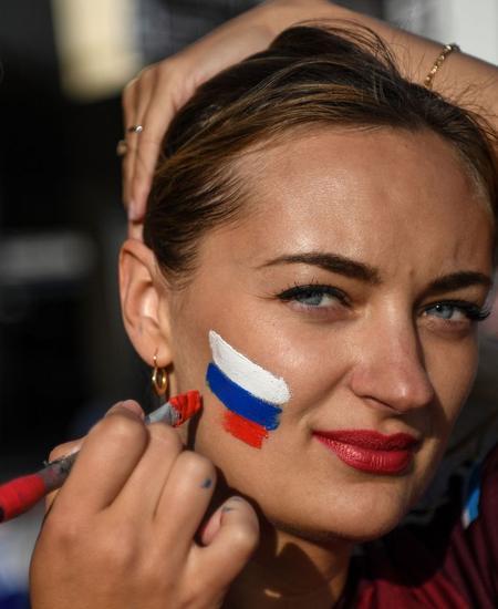 Diese Frau lässt sich eine russische Flagge auf die Wange malen. Nach der Farbenfolge könnte es auch eine slowakische sein. Die tschechische hat dieselben Farben, aber in anderer Form.