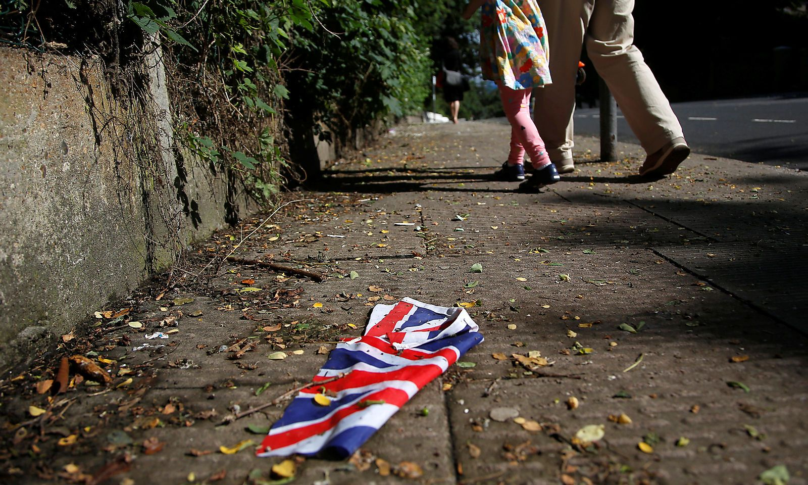 A British flag which was washed away by heavy rains the day before lies on the street in London