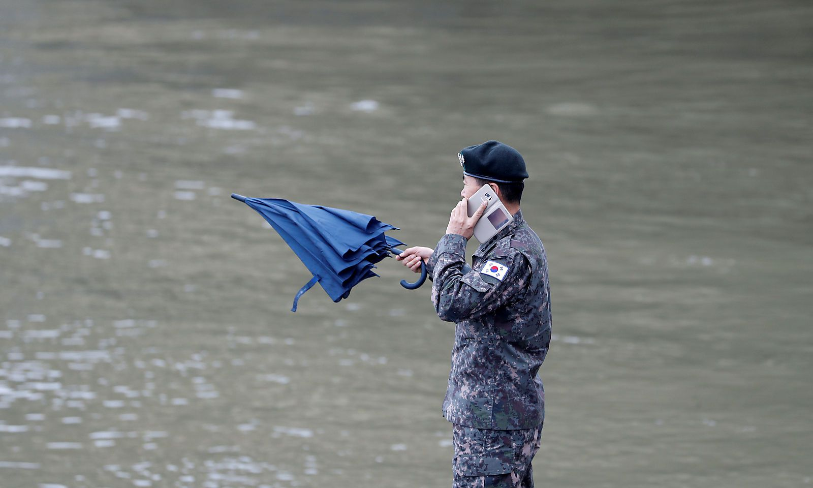 Military official from the South Korean Embassy is seen on his mobile phone at the Danube river bank in Budapest