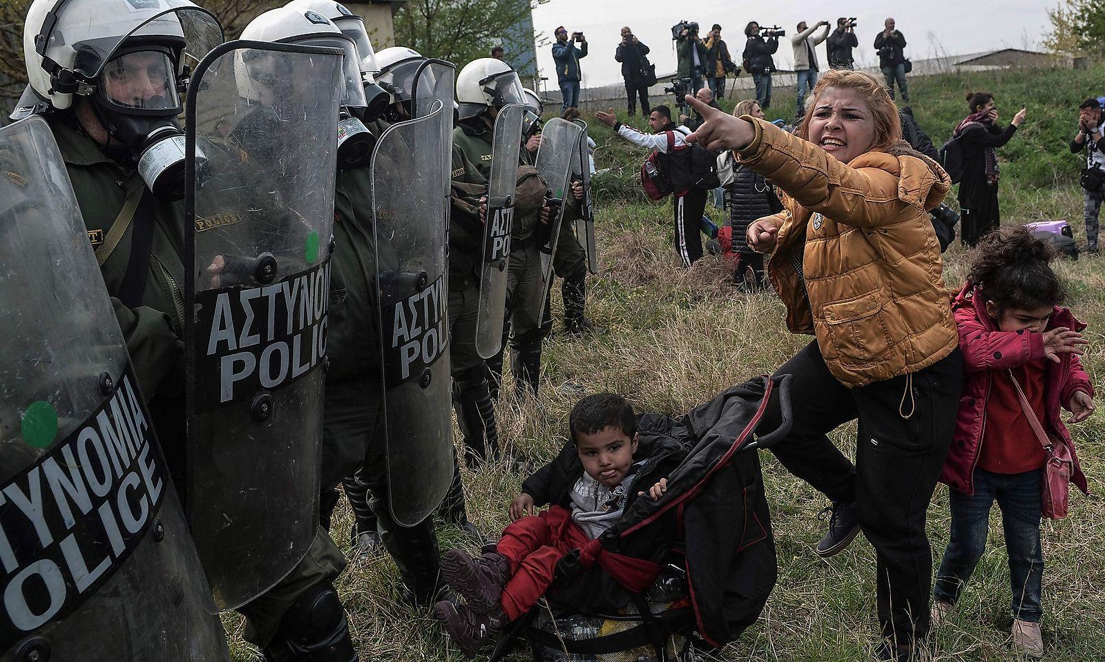Frauen versuchen mit Kindern in vorderster Linie die Polizeisperren zu überwinden