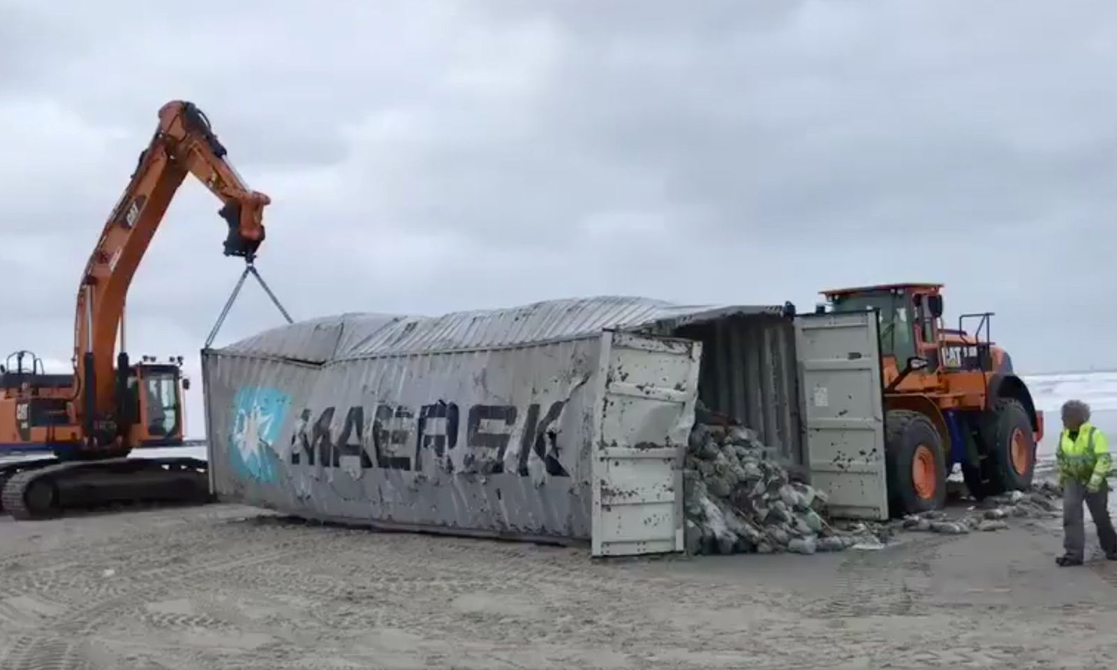 Heavy machinery lift cargo container after it washed up on beach in Vlieland