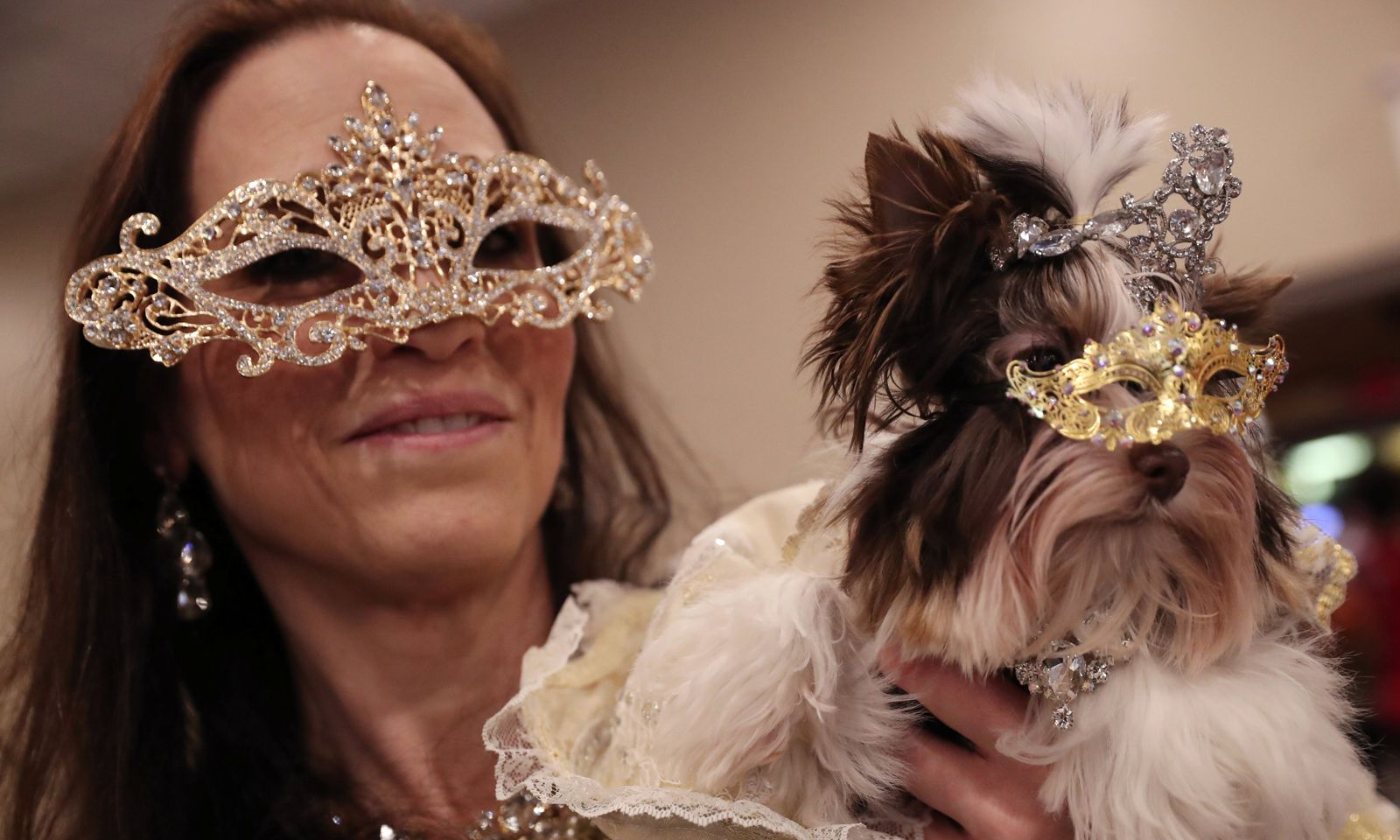 A woman holds a dog backstage at the 16th annual New York Pet fashion show in New York