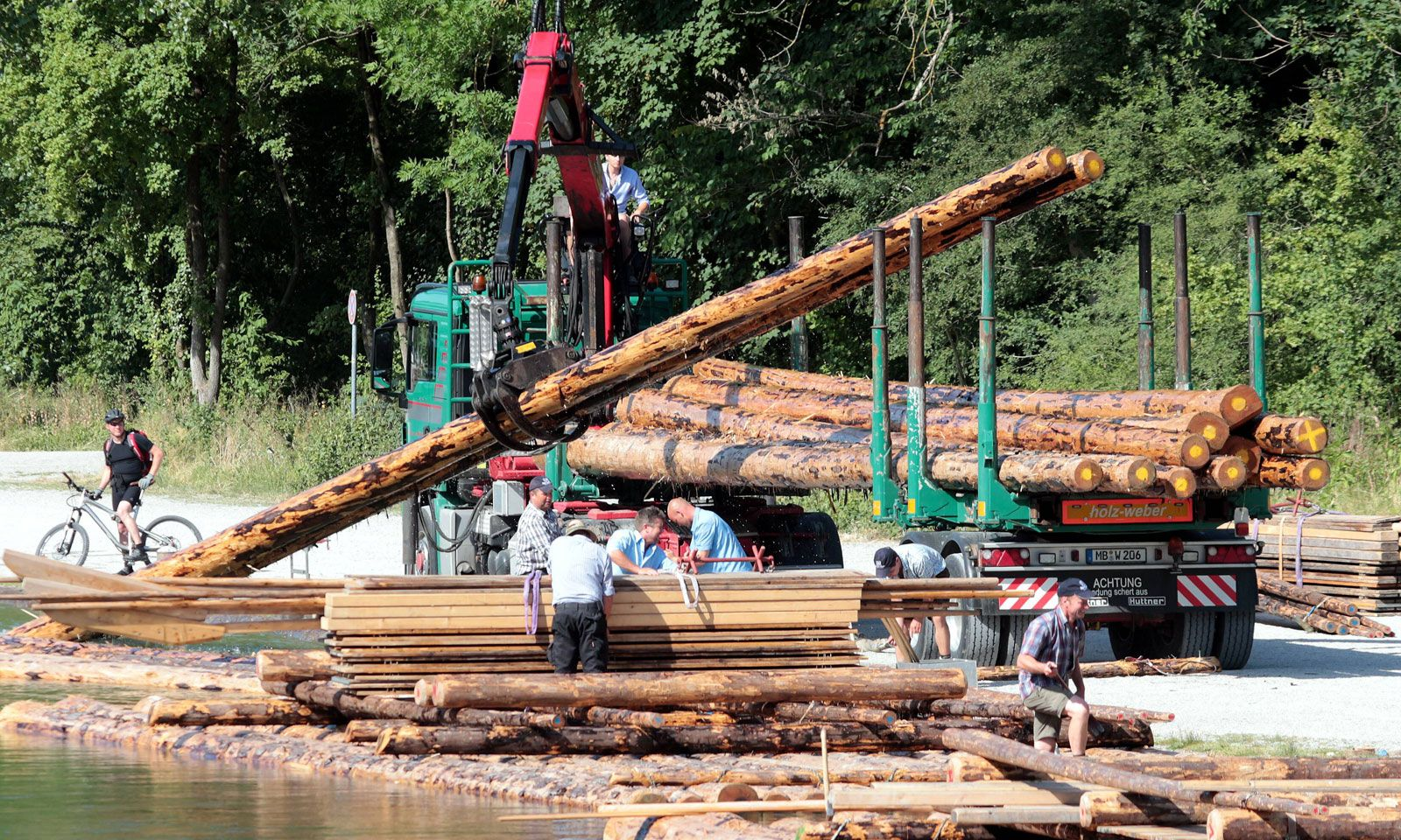 Arbeiter beim Verladen und Transportieren von Baumstämmen an der Isar.