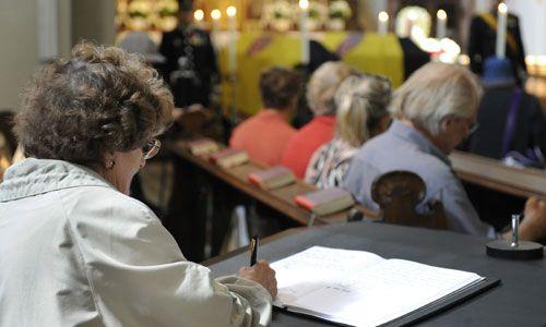 Alte Dame trägt sich ins Kondolenzbuch ein