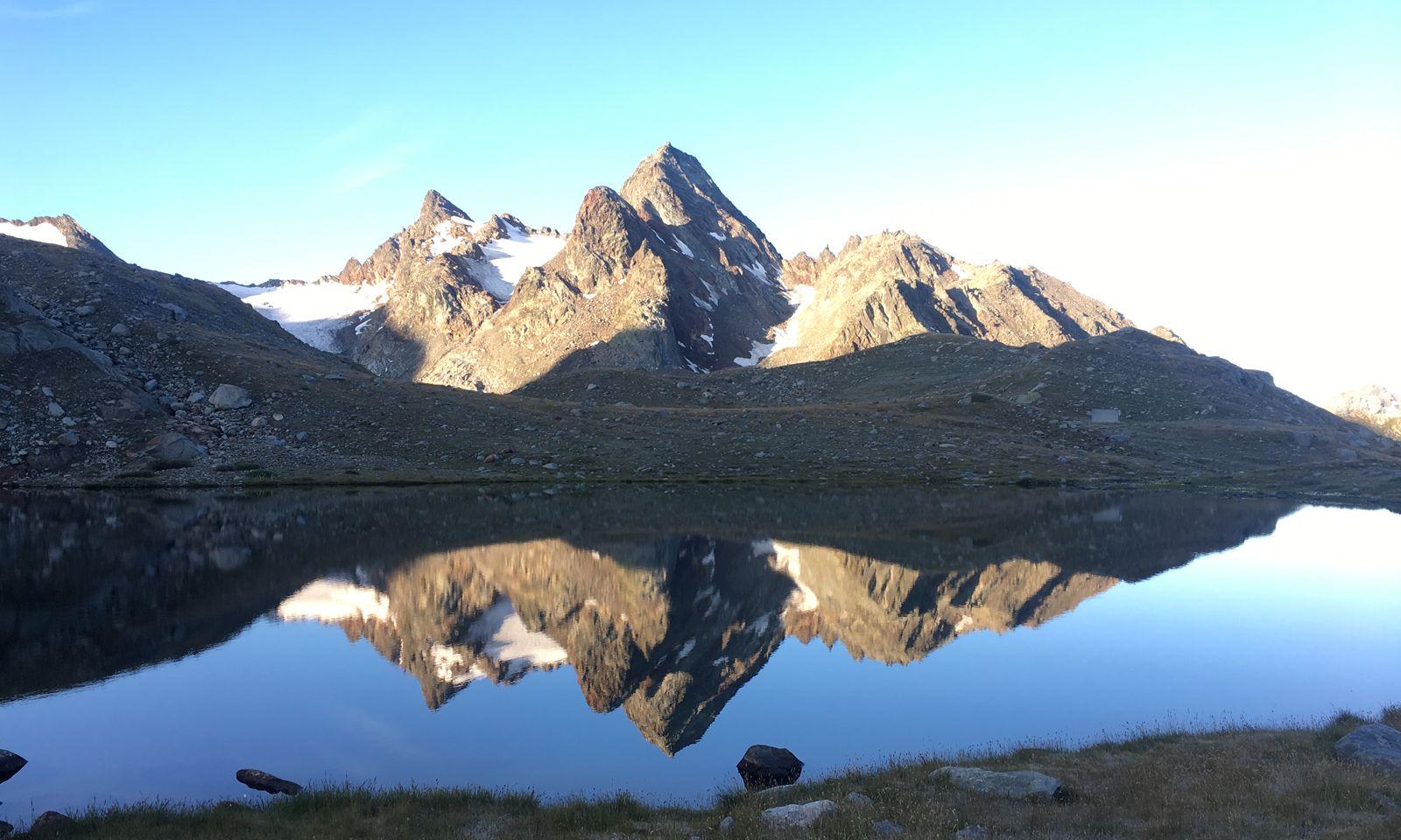 In den Morgenstunden glänzen die Gipfel doppelt.