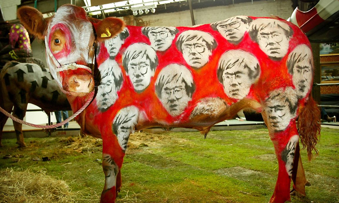 A COW STANDS PAINTED WITH IMAGES OF US ARTIST ANDY WARHOL AT THE TURFWAR EXHIBITION IN LONDON.