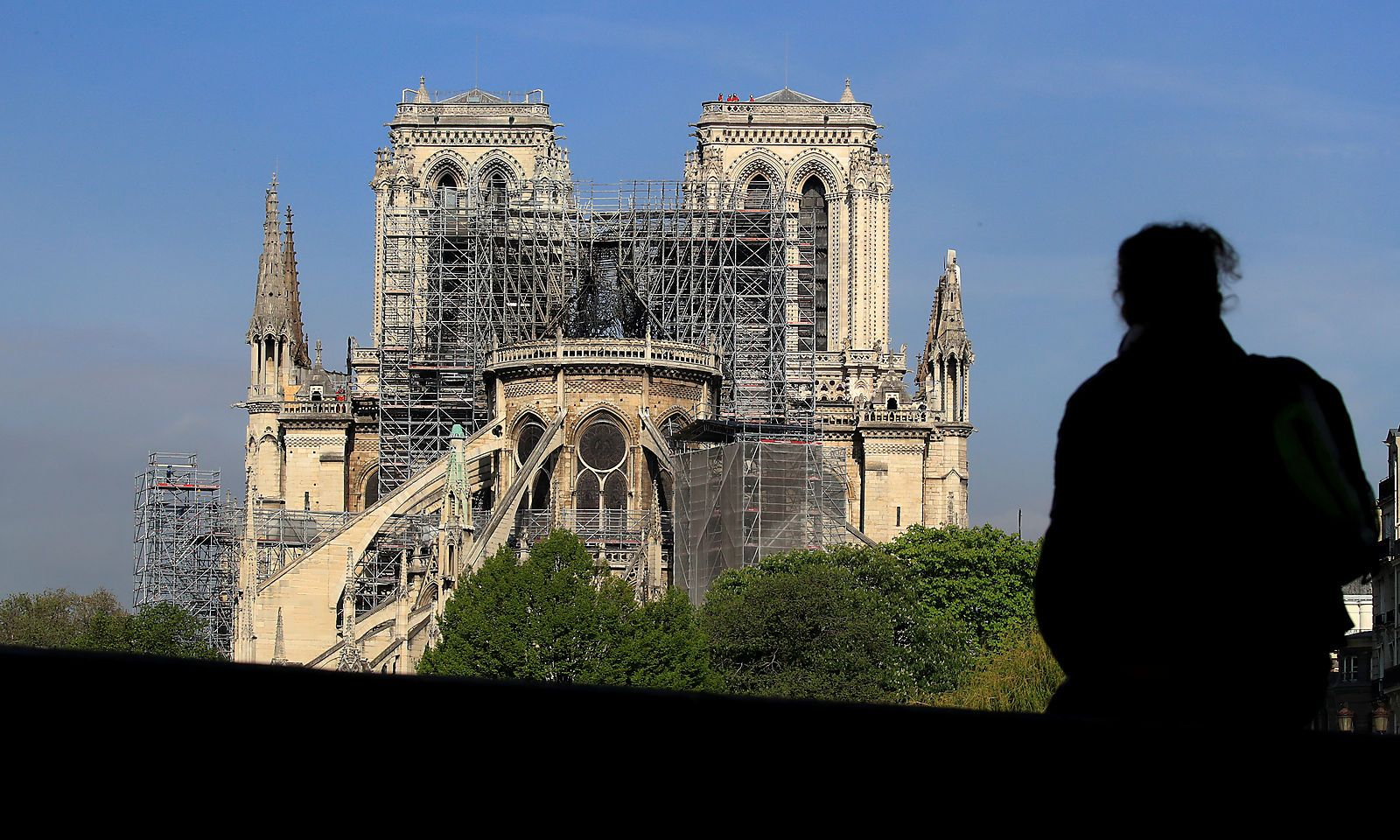 A person looks at Notre-Dame Cathedral after a massive fire devastated large parts of the gothic structure in Paris
