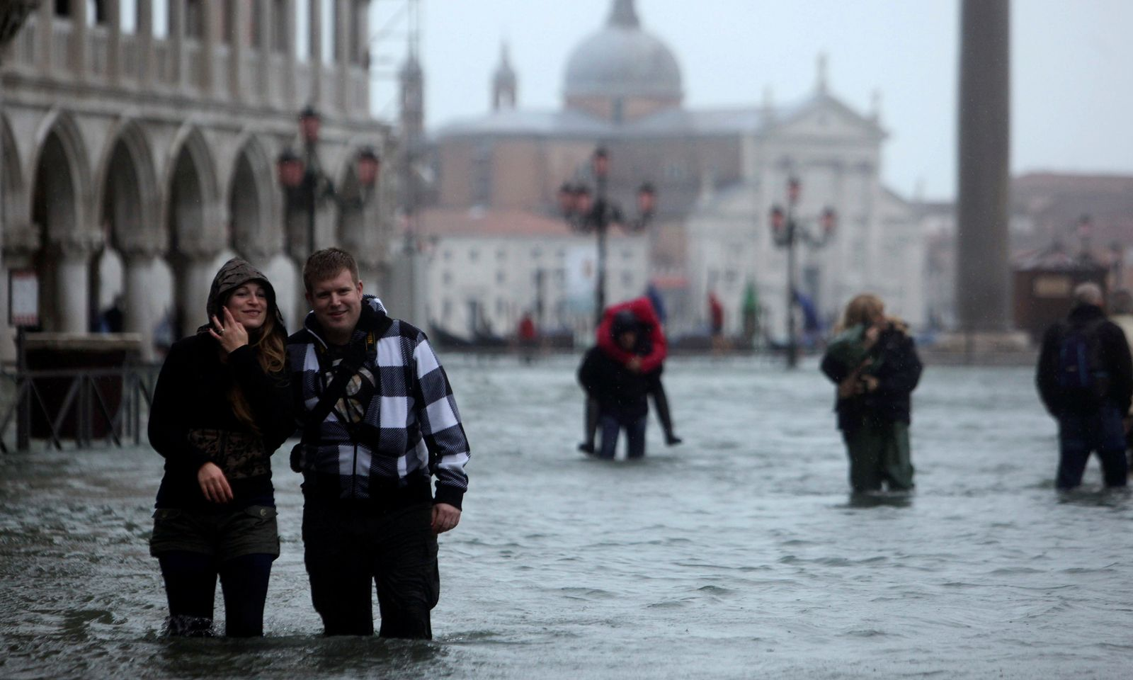 FILE PHOTO: People walk through a flooded street during a period of seasonal high water in Venice