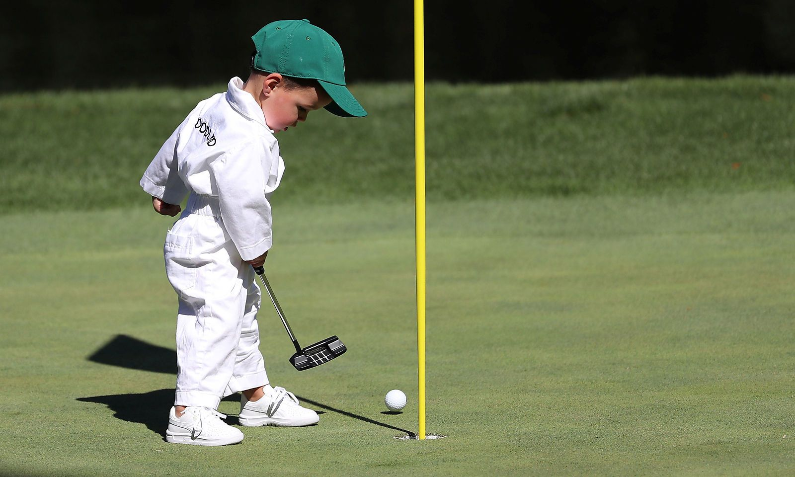 Gary Woodland's son putts on the 9th green during the 2019 Masters golf tournament's par 3 contest at the Augusta National Golf Club in Augusta, Georgia, U.S.