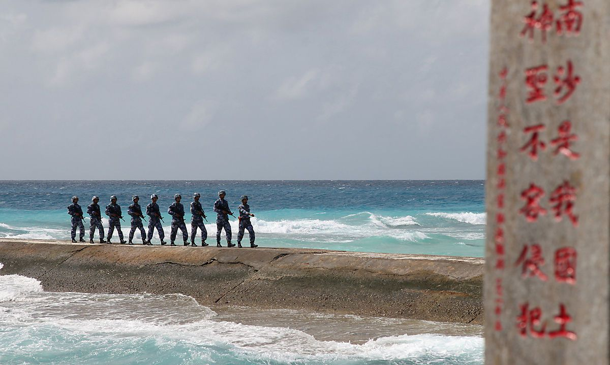 Soldiers of China´s People´s Liberation Army (PLA) Navy patrol near a sign in the Spratly Islands, known in China as the Nansha Islands