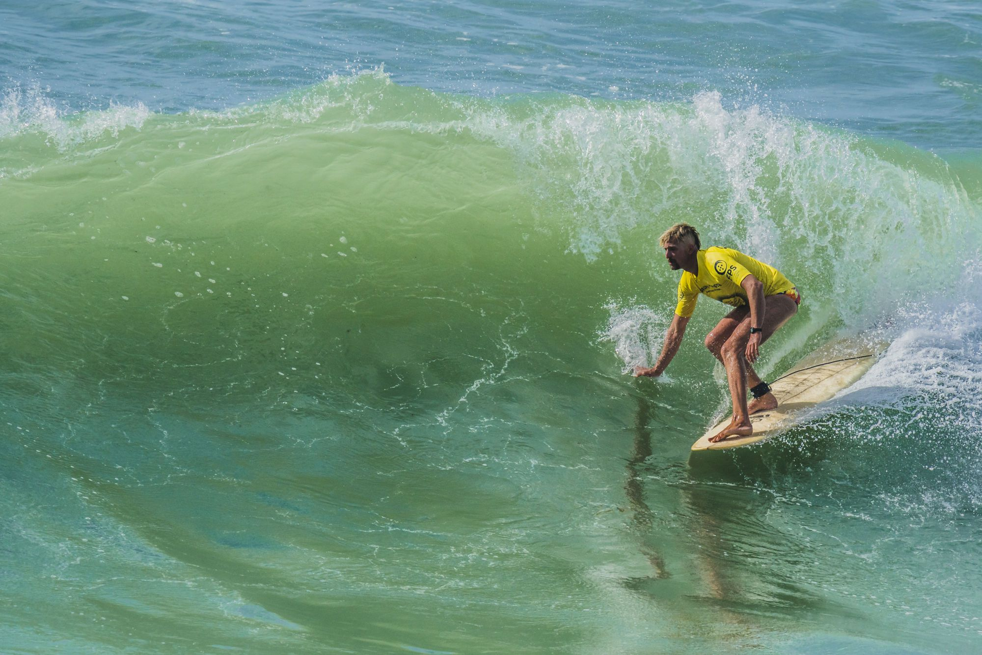 Lukas Stangl surft in der Badehose.